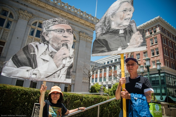 Demonstrators holding blowups of photos of Oakland fossil fuel resisters Photo: Brooke Anderson