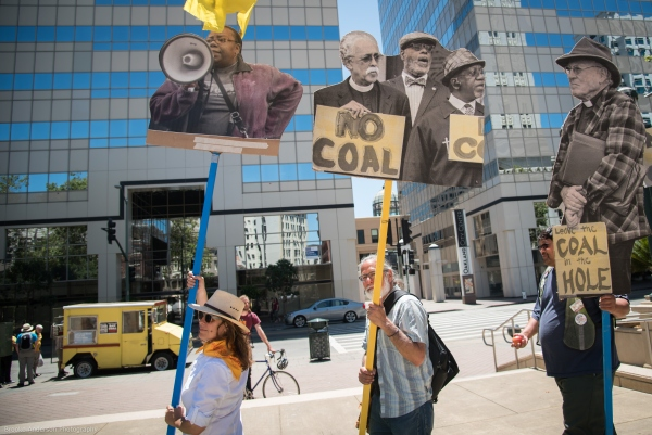Demonstrators on 14th Street carrying blow ups of Oakland coal resistance fighters Photo: Brooke Anderson
