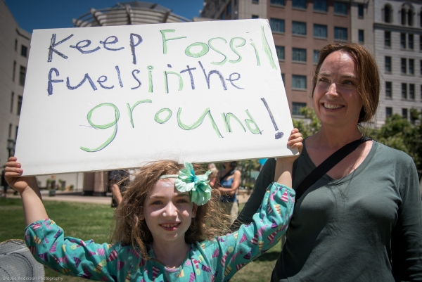 Kid with handmade Keep Fossil Fuels in the Ground sign Photo: Brooke Anderson