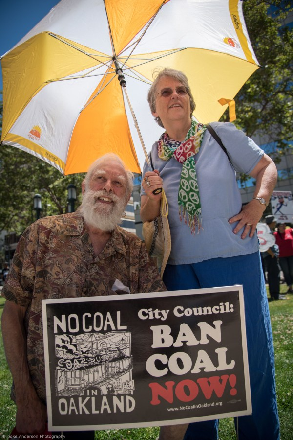 Couple with solar-powered umbrella and Ban Coal yard sign Photo: Brooke Anderson