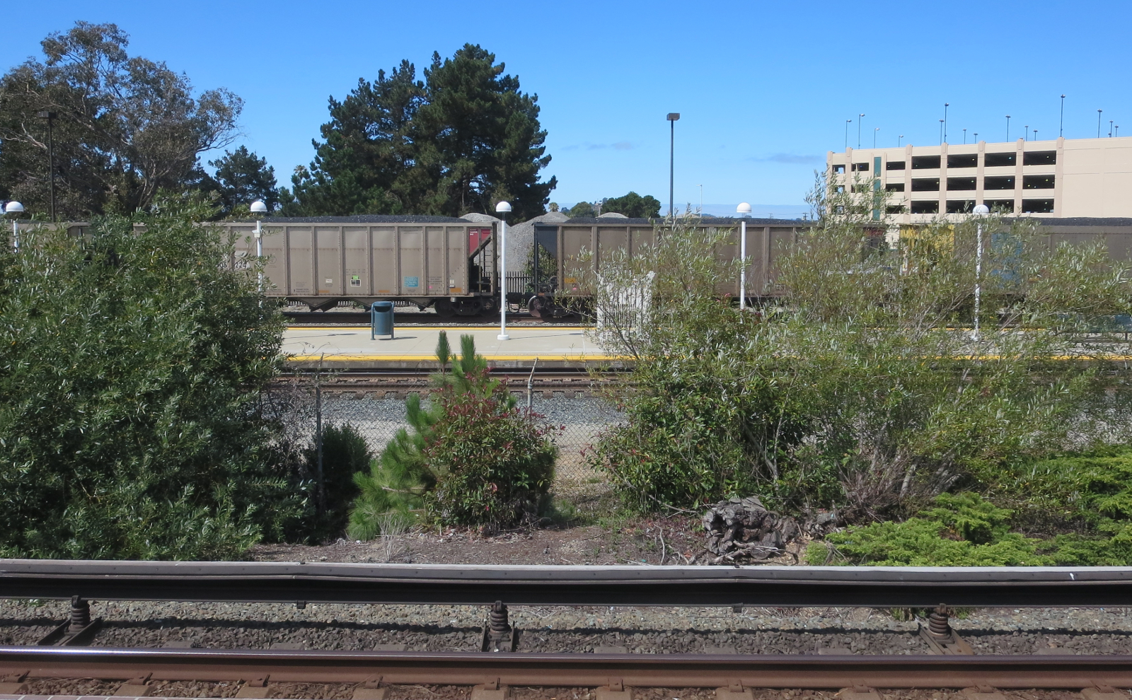 An uncovered coal train rolls past the Richmond BART station, July 11, 2015. Photo credit: Steve Masover.