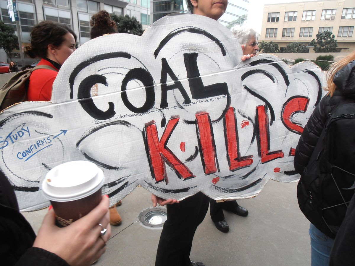 "Supporter of City of Oakland carries ""Coal Kills"" sign"