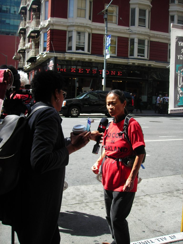 NCIO organizer lora jo foo speaks with a reporter at the PRI Conference picket, 2018-09-12. Photo credit: Kathy Kojimoto.